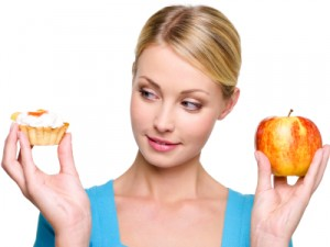Woman holding apple in one hand, tart in other hand and looking sideways at the tart