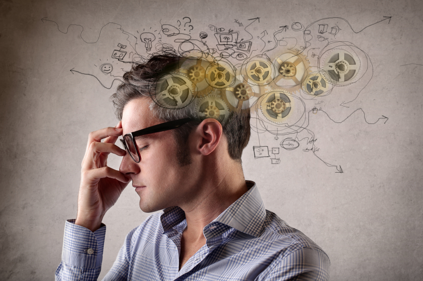 Man wearing glasses holding the bridge of his nose while gears, arrows, and other images hover around his head