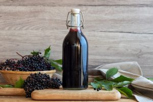 Black elderberries in a bowl and on counter surrounding bottle of elderberry extract