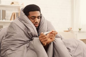 Man bundled in duvet looking at thermometer
