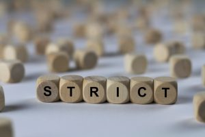 """Wooden cubes spelling out """"strict"""""""